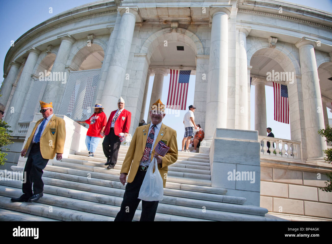 Veterans pass out American flags to visitors at the Arlington National Cemetery Memorial Amphitheater on Memorial - Stock Image