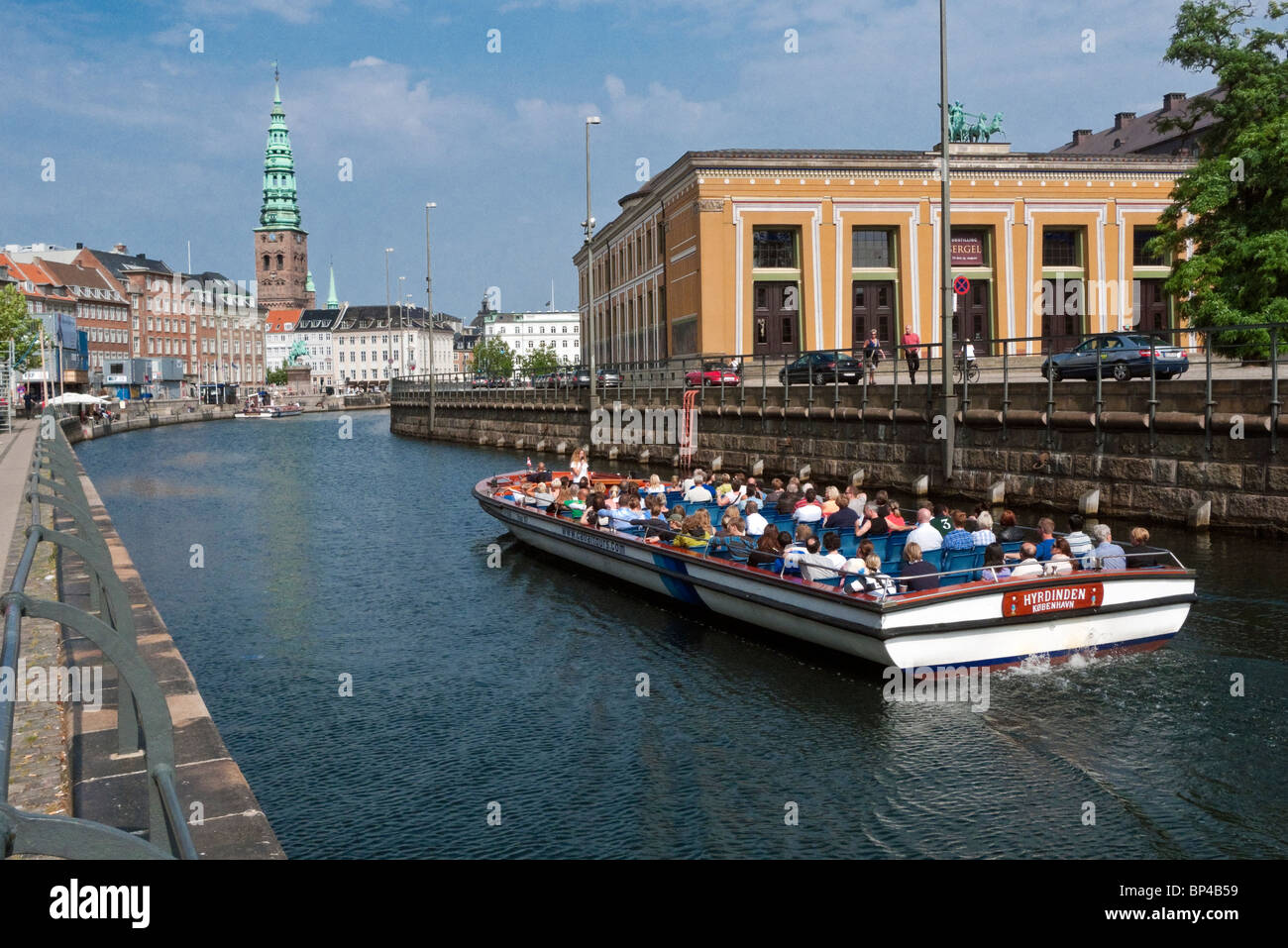 Harbour cruise vessel passes through Frederiksholm Kanal in Copenhagen with Thorvaldsens Museum to the right. - Stock Image