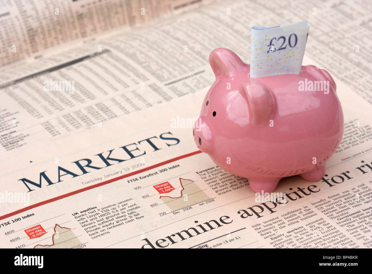 pink piggy bank with 20 pound note sitting on a copy of the financial times newspaper money markets section in the - Stock Image