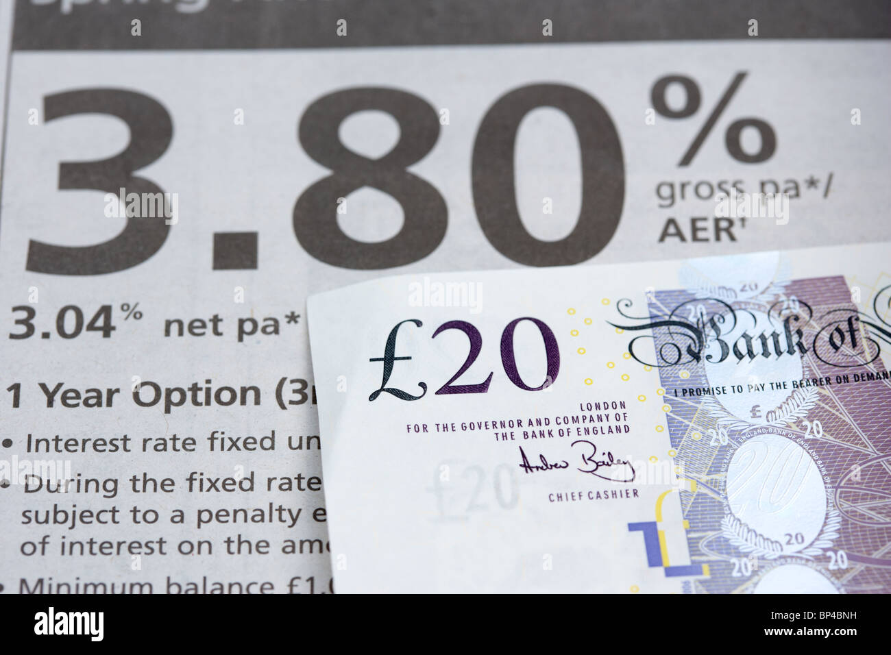 20 pound note beside a bank loan advertisement in an newspaper - Stock Image