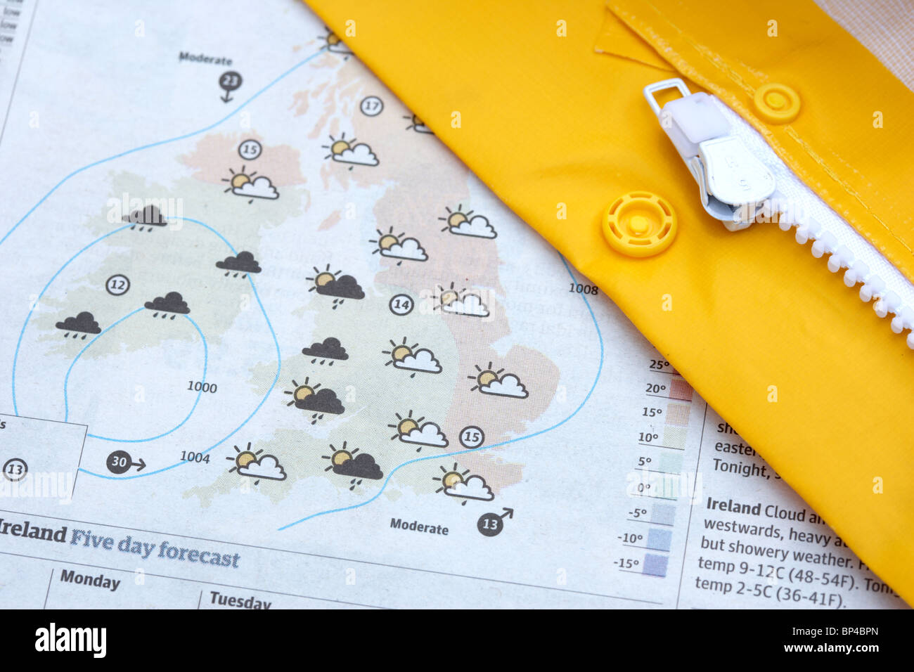 yellow waterproof coat and zip lying across the weather forecast in a newspaper - Stock Image