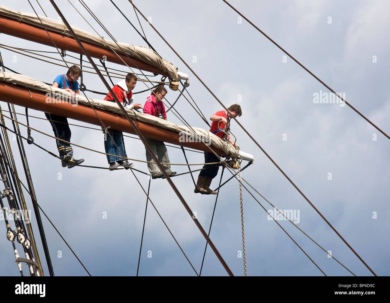 Members of the crew of a square rigged sailing ship working on the middle spar of one of the masts. - Stock Image