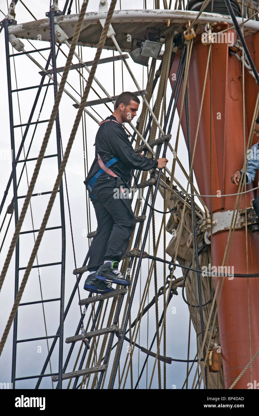 crewman on a square rigged sailing ship working high in the rigging. - Stock Image