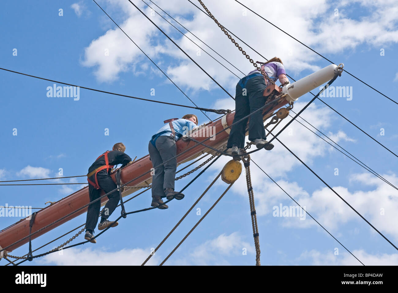 Members of the crew of a square rigged sailing ship working on the middle yard (spar) of one of the masts. - Stock Image