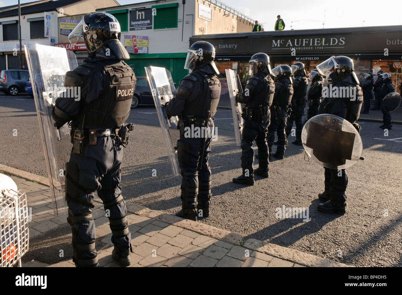 Police riot squad line up across a road in preparation for civil disturbance - Stock Image