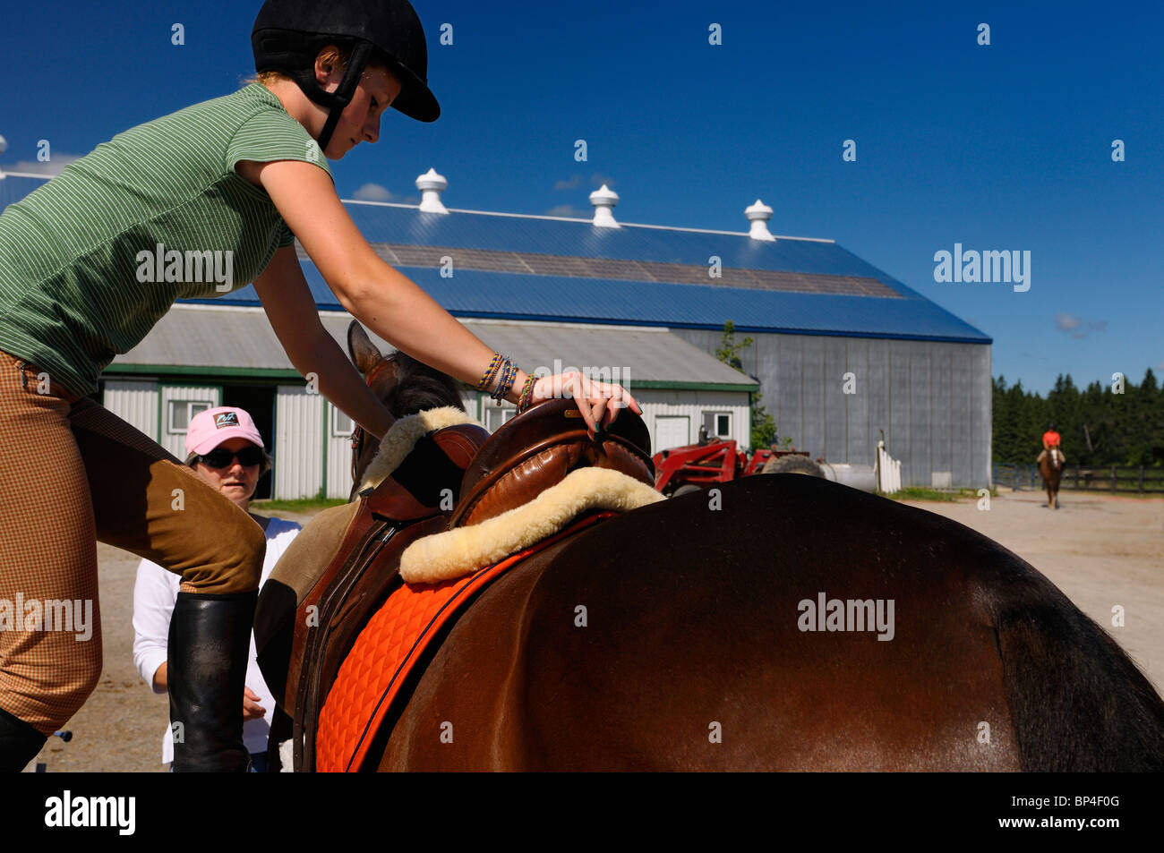 Woman holding horse  while young female rider mounts her thoroughbred horse at riding stables for training session - Stock Image