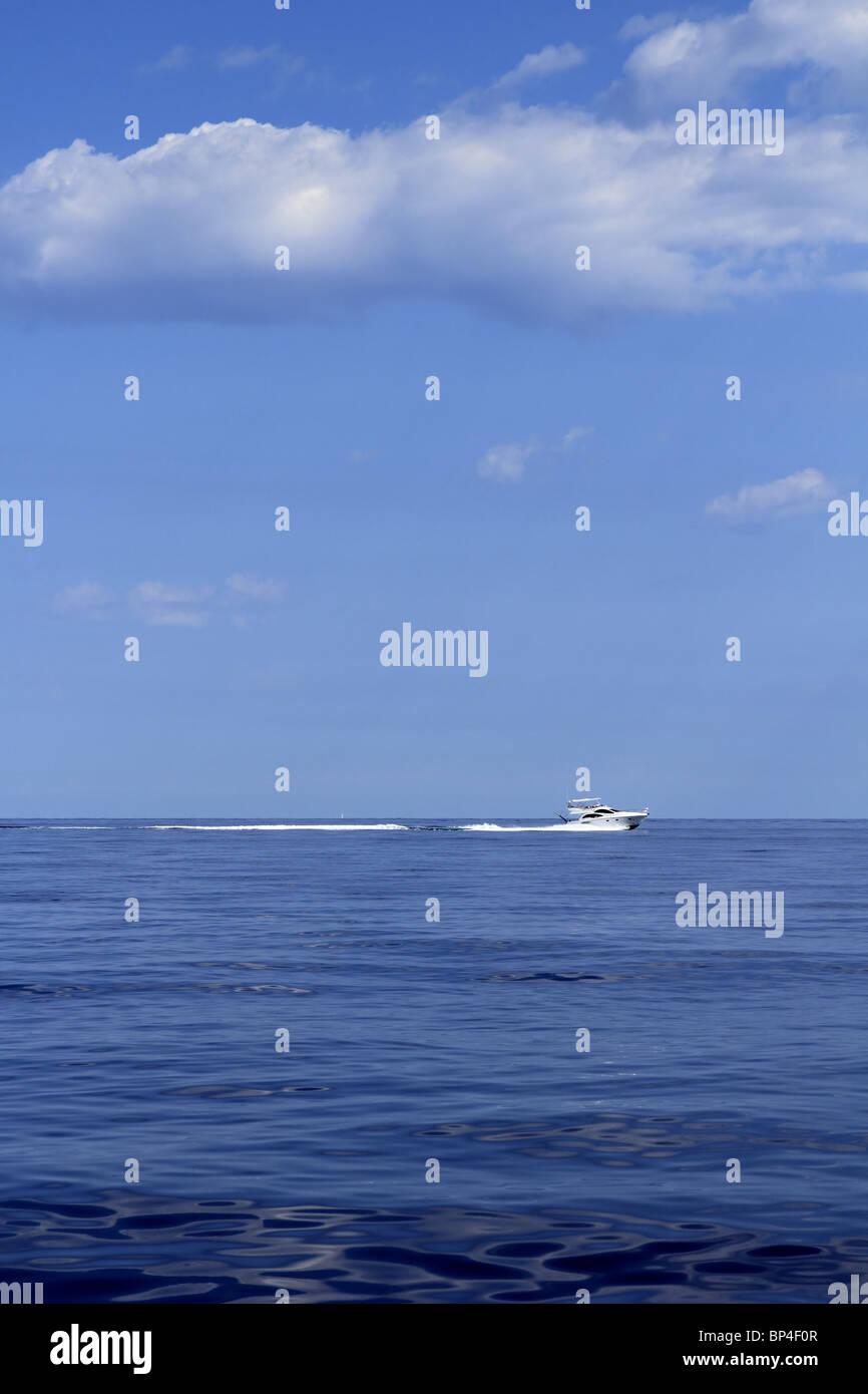 motorboat fisherboat cruising speed on blue sea horizon ocean - Stock Image