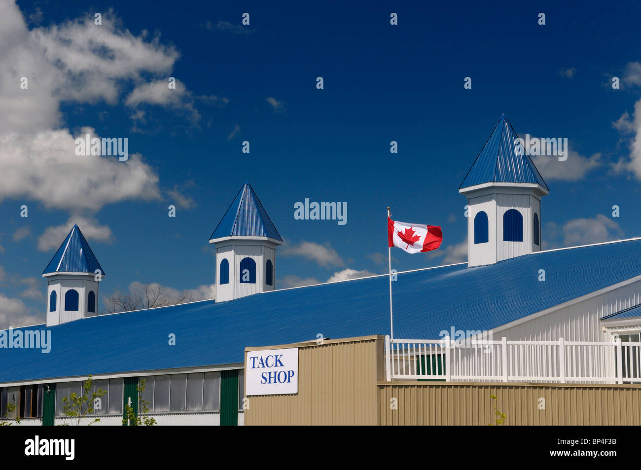 Blue Equestrian barn and horse riding stables with tack shop Ontario with Canadian flag and blue sky - Stock Image