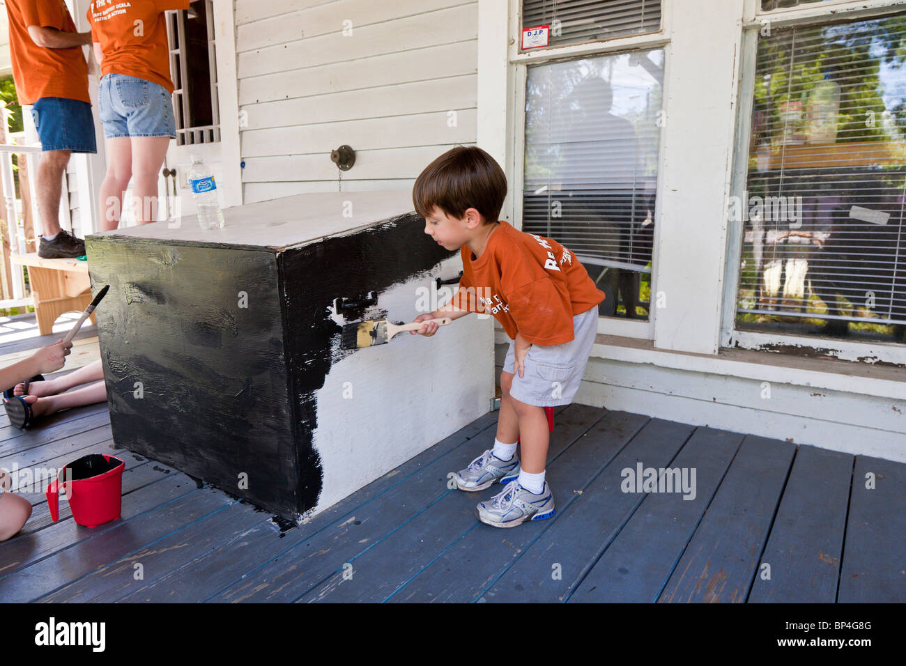 Young boy painting to help members of First Baptist Church provide community service during Be The Church outreach - Stock Image