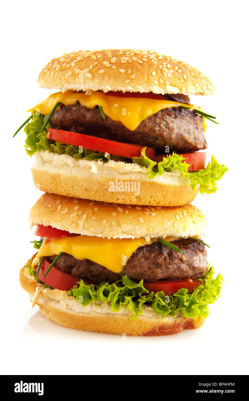 Tasty cheeseburgers with vegetables and bread roll - Stock Image
