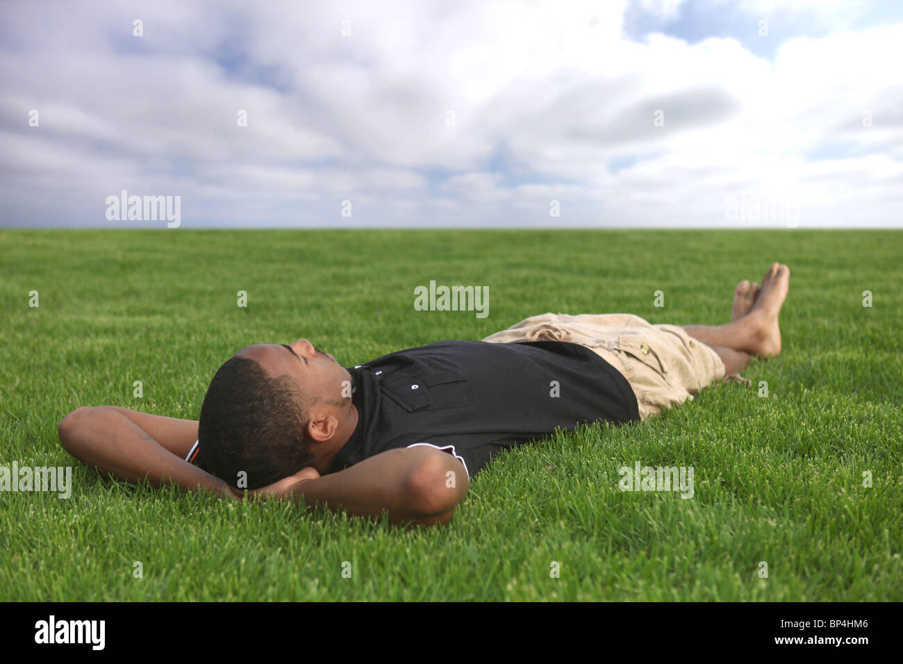 African American Male Student Resting in the Grass Outdoors - Stock Image