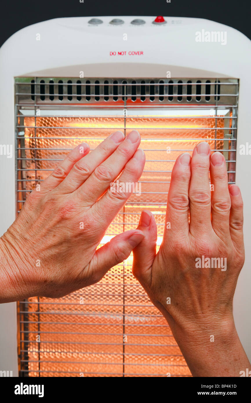 One senior woman warming hands in front of a low energy Halogen room heater. England UK Britain - Stock Image