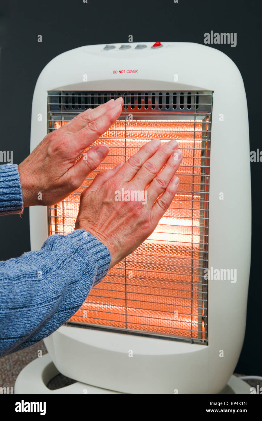 One senior woman trying to keep warm by warming hands in front of a low energy Halogen room heater in winter. England - Stock Image