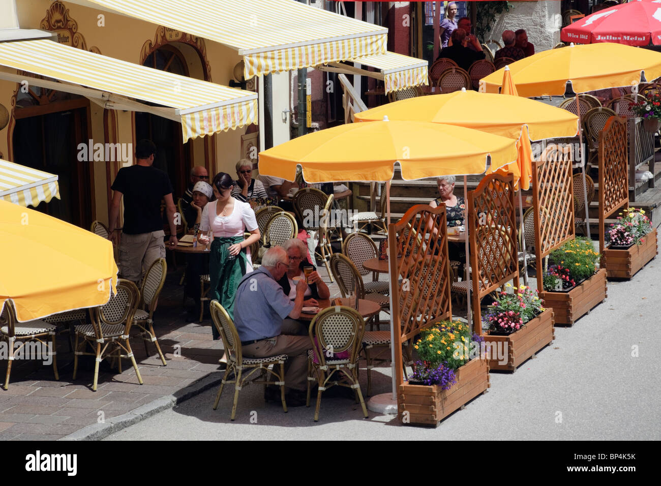Pavement cafes with people dining outside in the old town. St Wolfgang, Salzkammergut, Upper Austria, Austria, Europe. - Stock Image