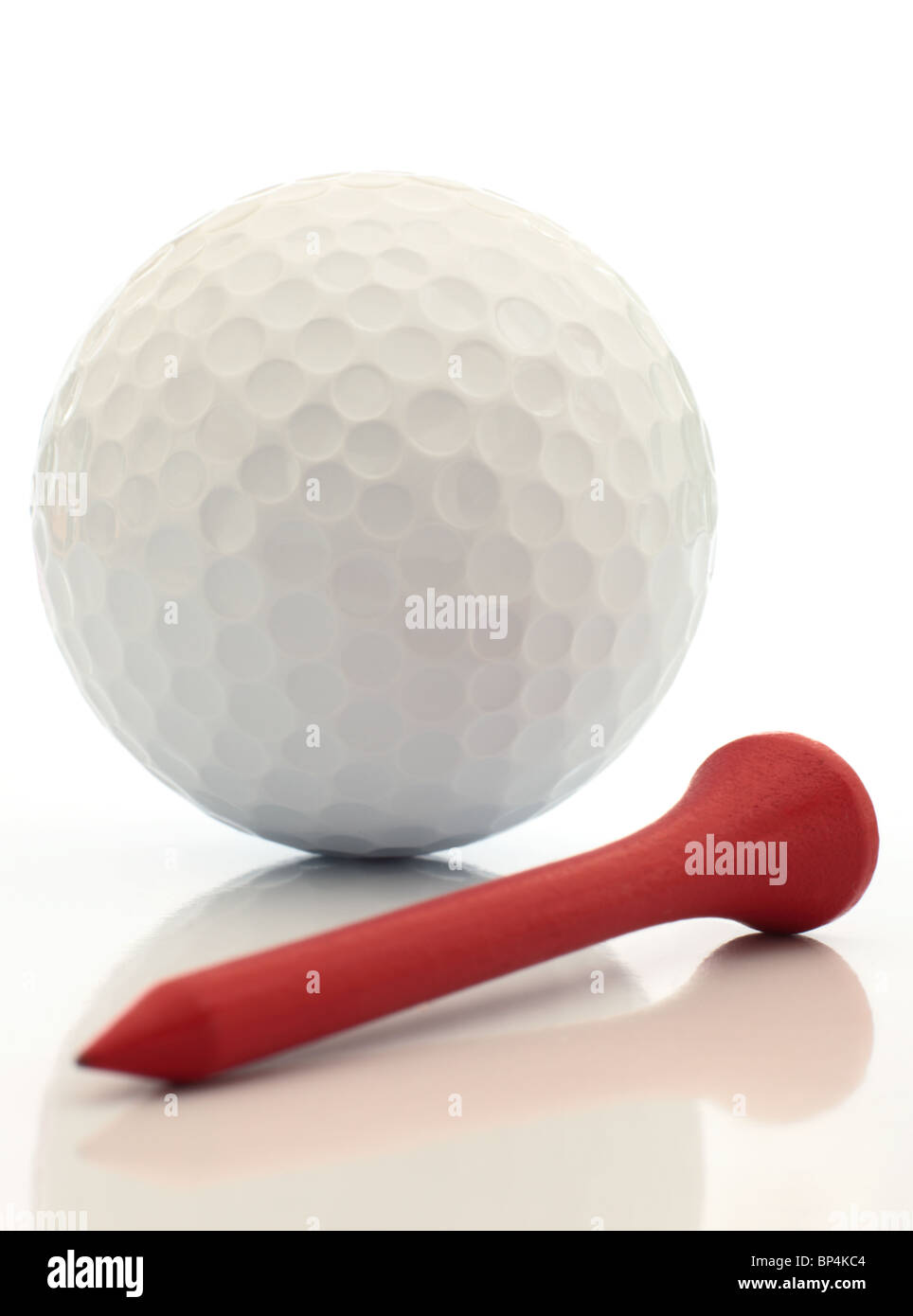 A golf ball and red tee close up reflected. This image is exclusive to Alamy. - Stock Image
