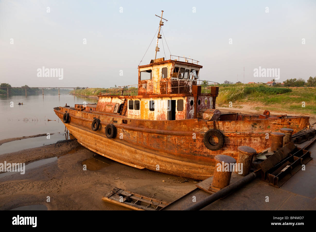 An abandoned ship getting disassembled for scrap metal on the Mekong- Kandal Province, Cambodia - Stock Image