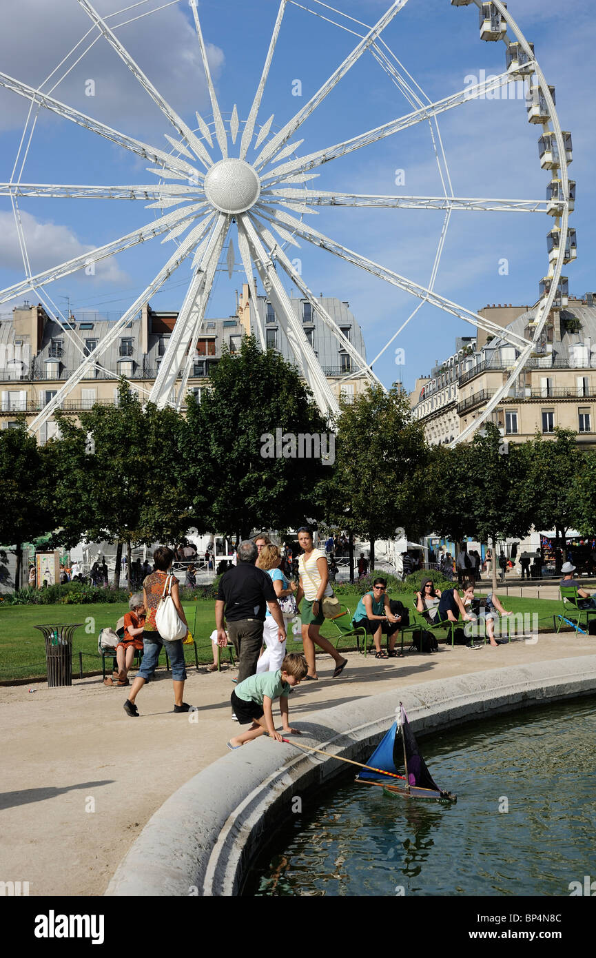 Paris France A kid playing with toy yacht at 'Tuileries Garden' - Stock Image