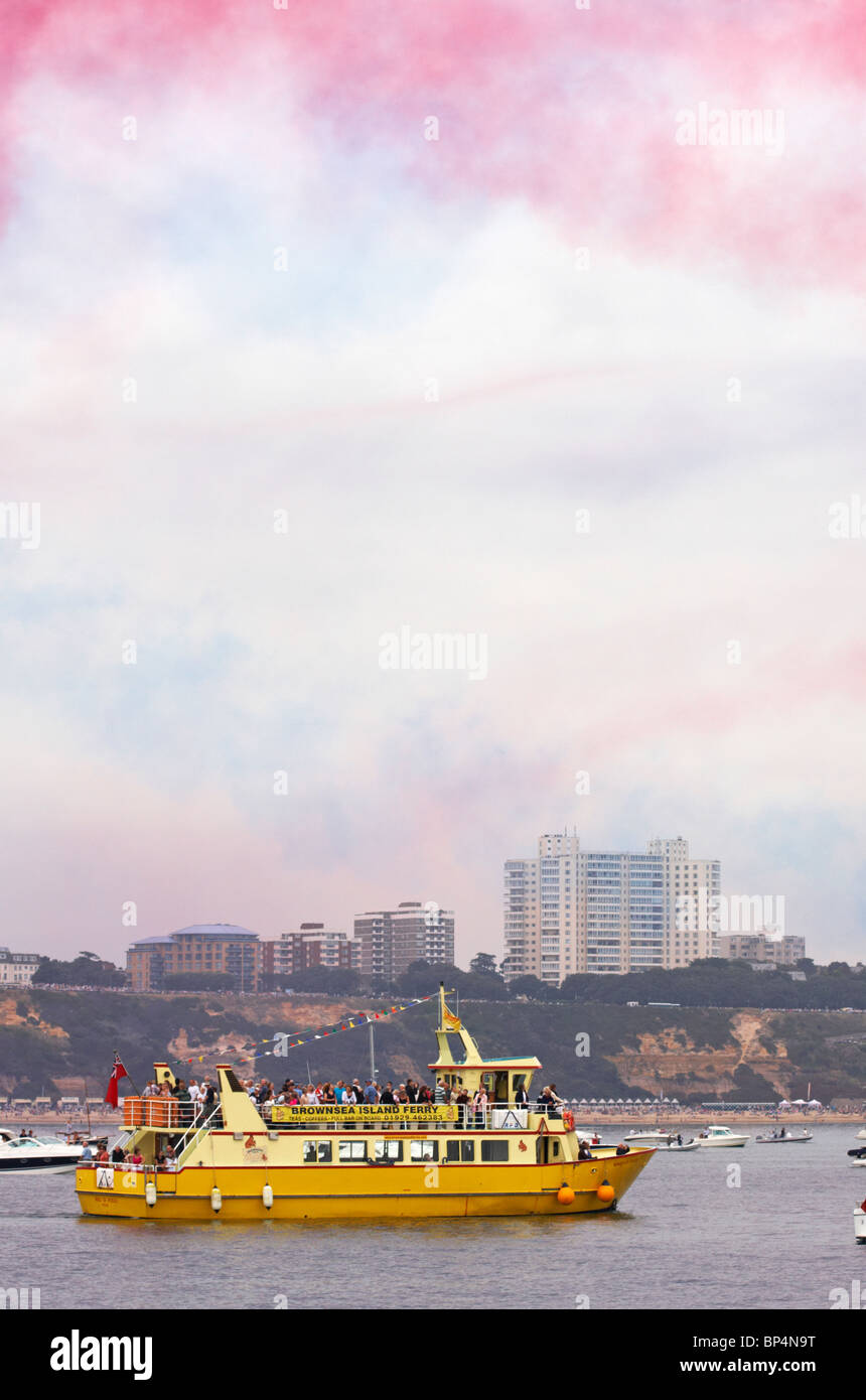Colourful vapour trails fill the skies from the Red Arrows display, as crowds watch the Bournemouth Air Festival - Stock Image