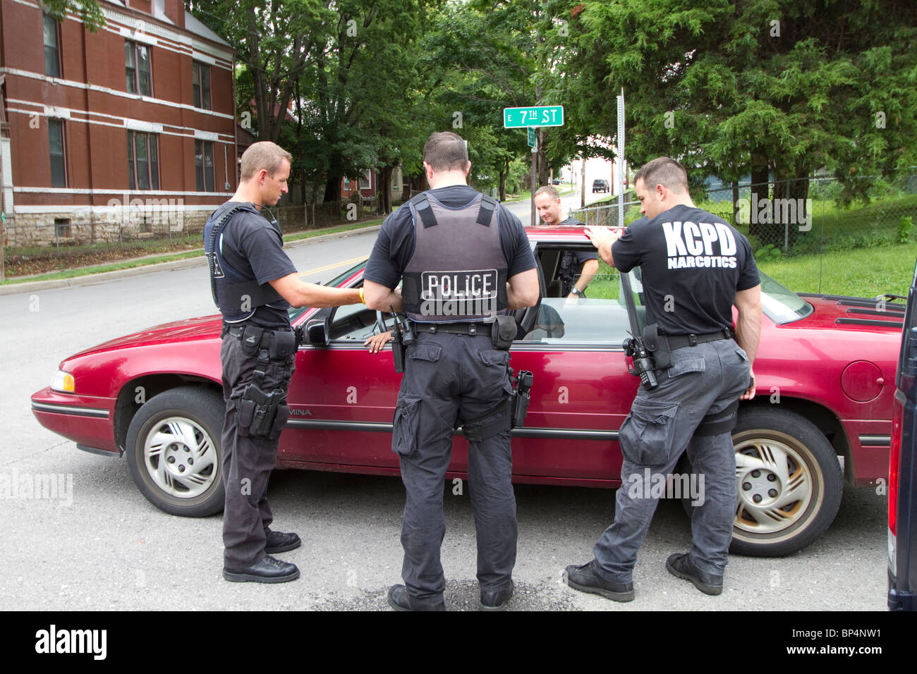 Police officers from tactical team talking to an individual found sleeping in a vehicle in an intersection. Kansas - Stock Image