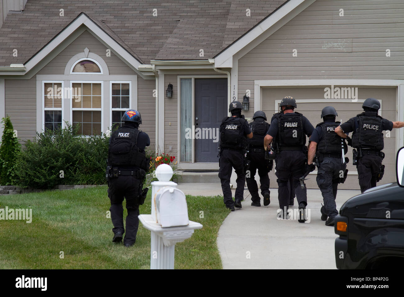 Police Tactical team from Street Narcotics Unit approach residence to serve a drug related high risk search warrant. - Stock Image