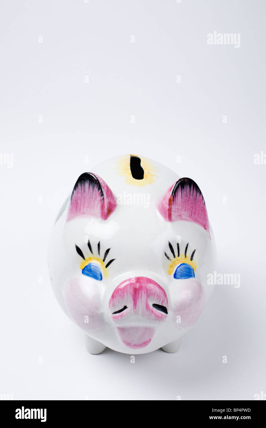 A kitsch looking Piggy Bank on white background. - Stock Image