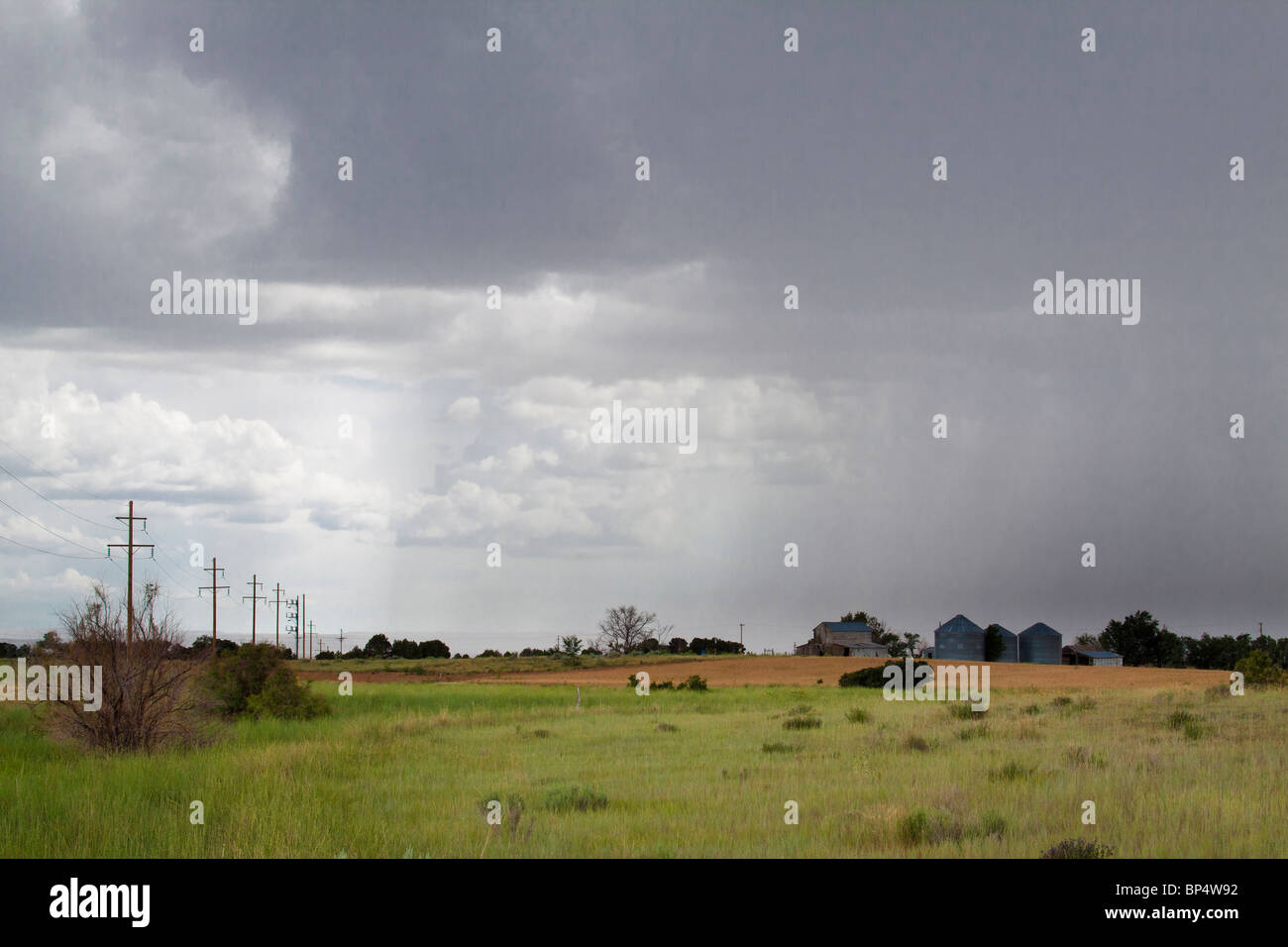 Rain pouring down onto farmhouse and silos in a thunder storm in rural farmland of southwest Colorado - Stock Image