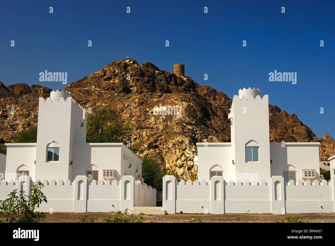 New family homes beneath an old fortress in the periphery of Muscat, Sultanate of Oman - Stock Image