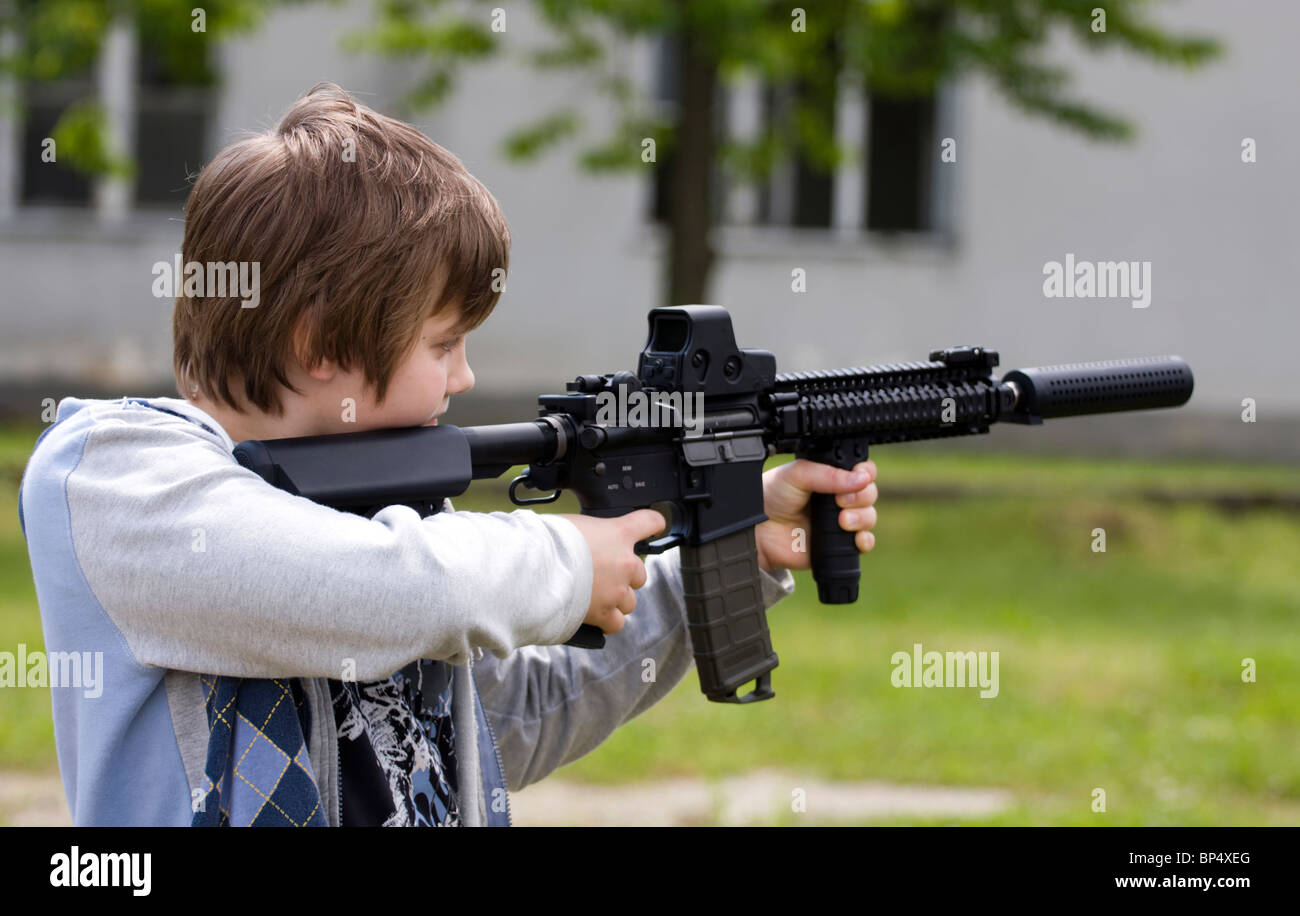 Teenager aiming with automatic rifle. - Stock Image