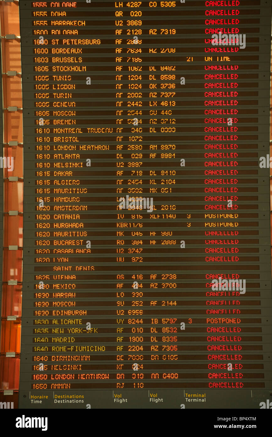 Passengers look at the departures board at Charles de Gaulle Airport in Paris, filled with cancelled or postponed - Stock Image