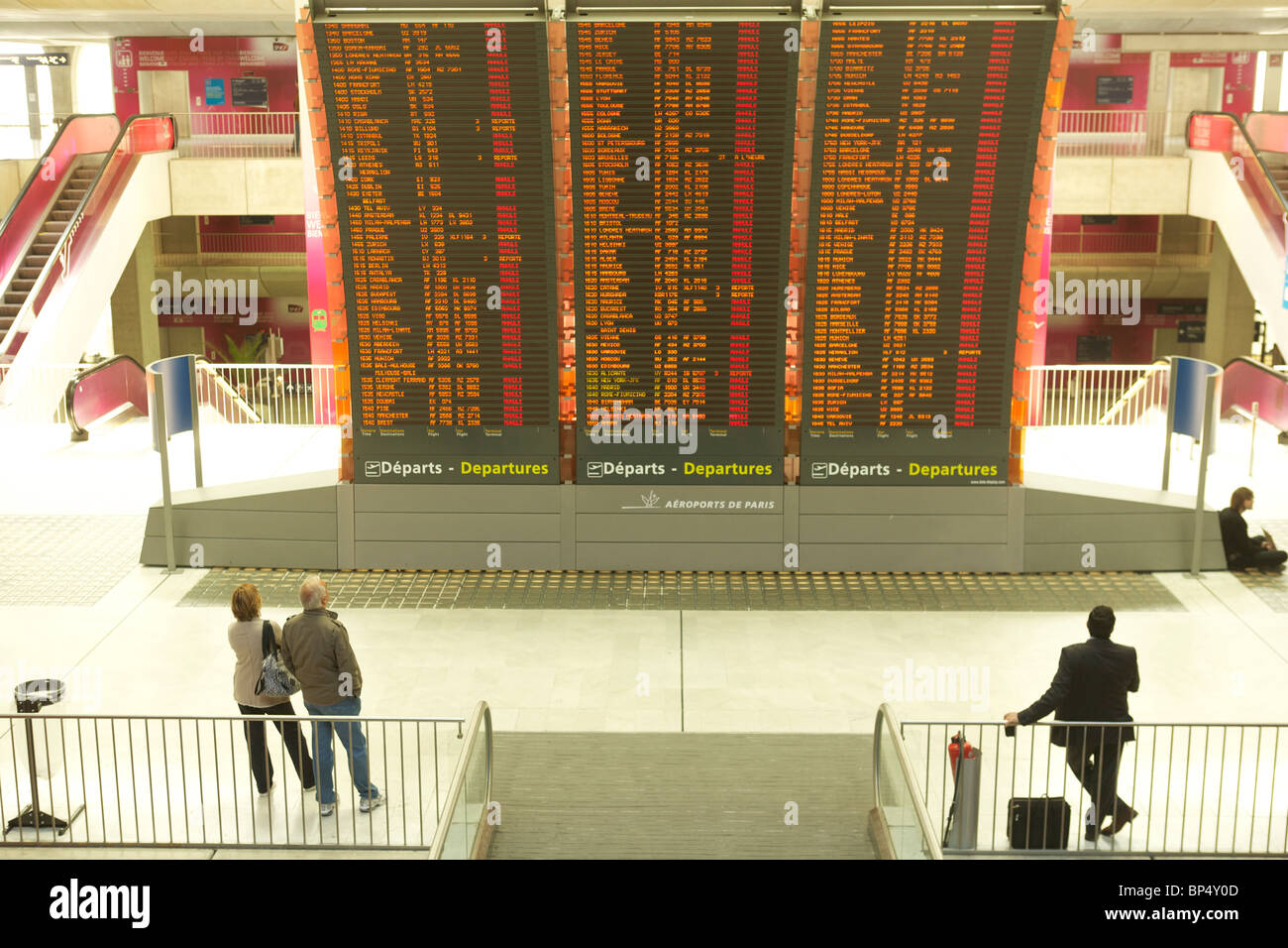 Passengers look at the departures board at Charles de Gaulle Airport in Paris, filled with canceled or postponed - Stock Image