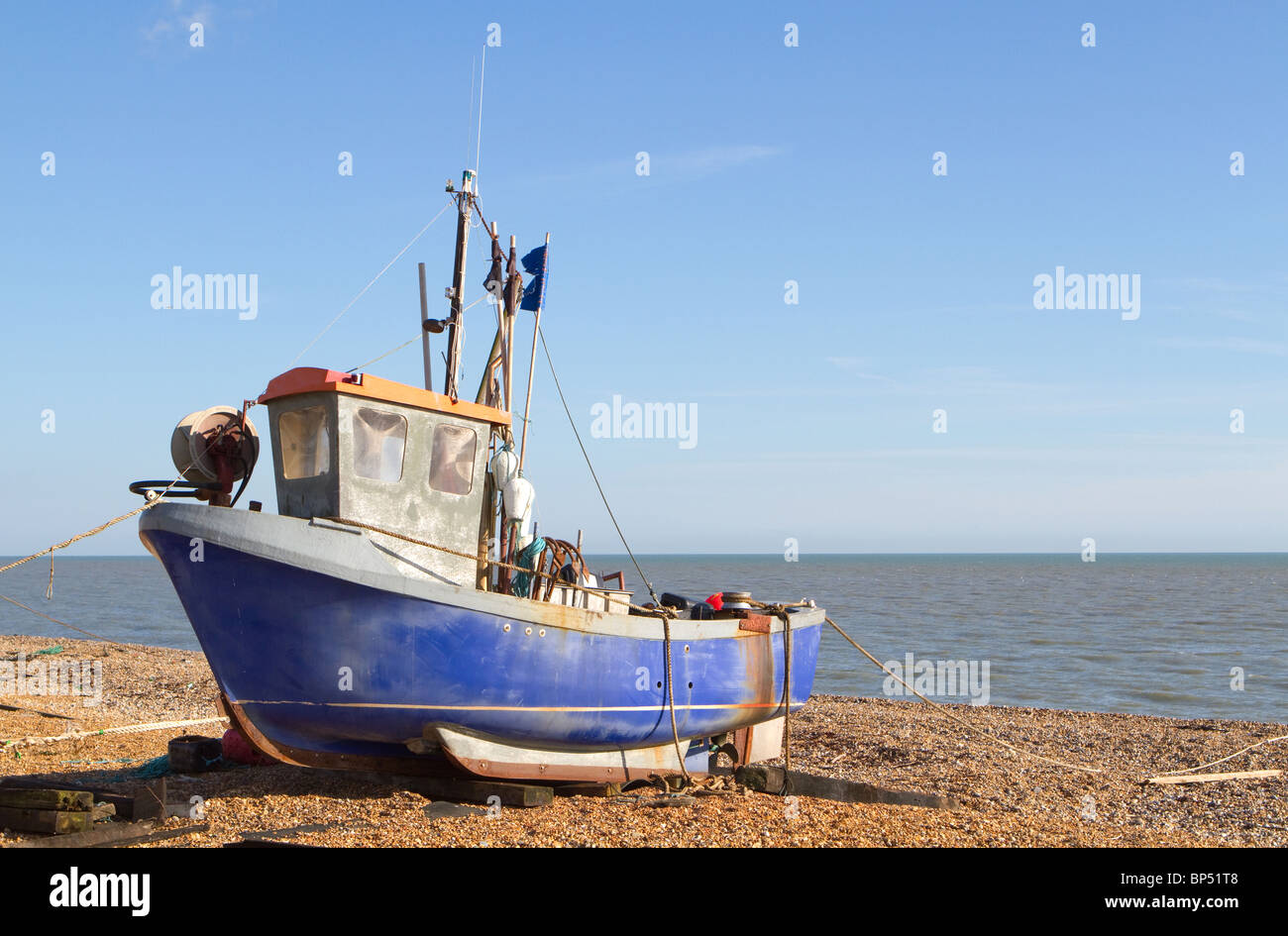 Traditional small fishing boat that has been pulled up onto the beach at Hythe, near Folkestone, Kent, UK. - Stock Image