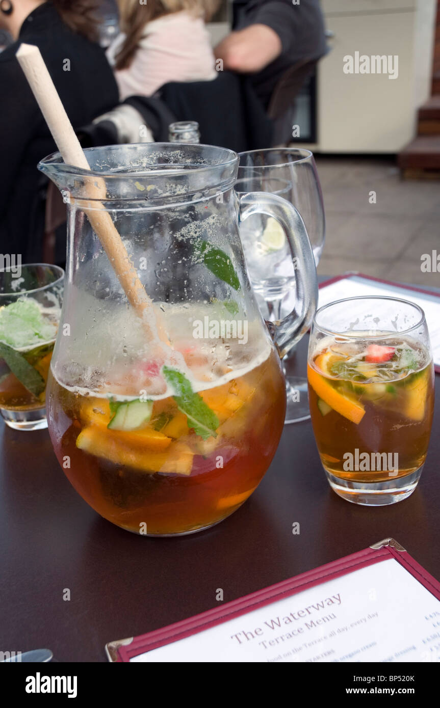 Half full cocktail, summer drink in a jug and a glass of Pimm's No:1, outside, fresco dining, London, England, UK, - Stock Image