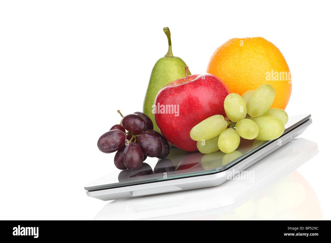 Apfel, Orange, Birne und Trauben auf einer schmalen Küchenwaage Stock Photo