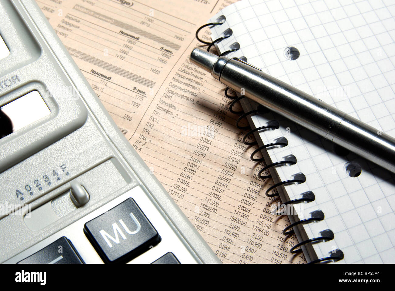 Financial calculator, steel pen and notebook laying on newspaper. Concept. Stock Photo
