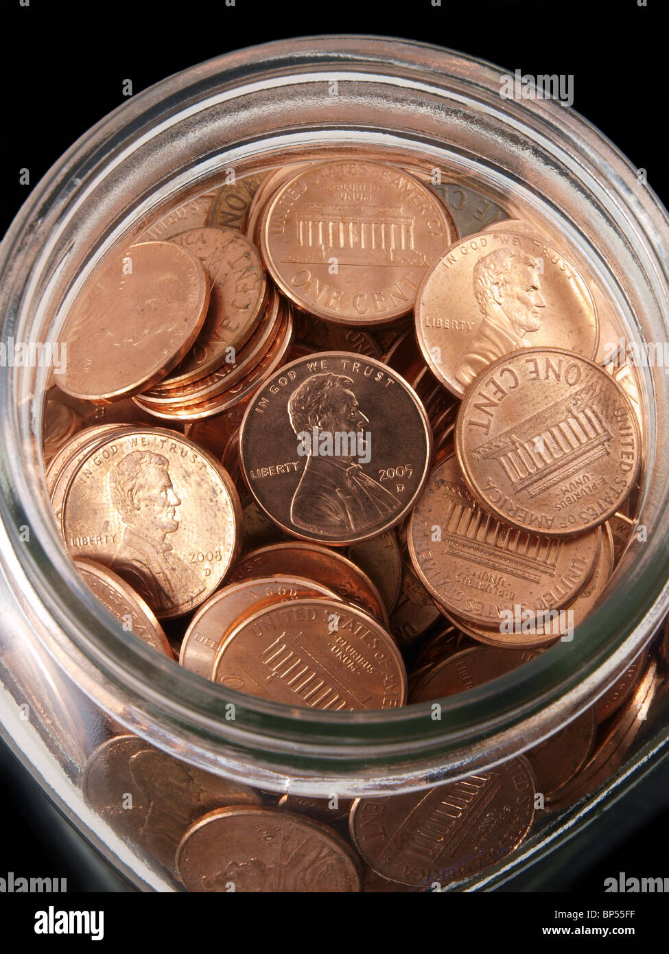 Tight shot of shinny pennies in a vintage jar. - Stock Image