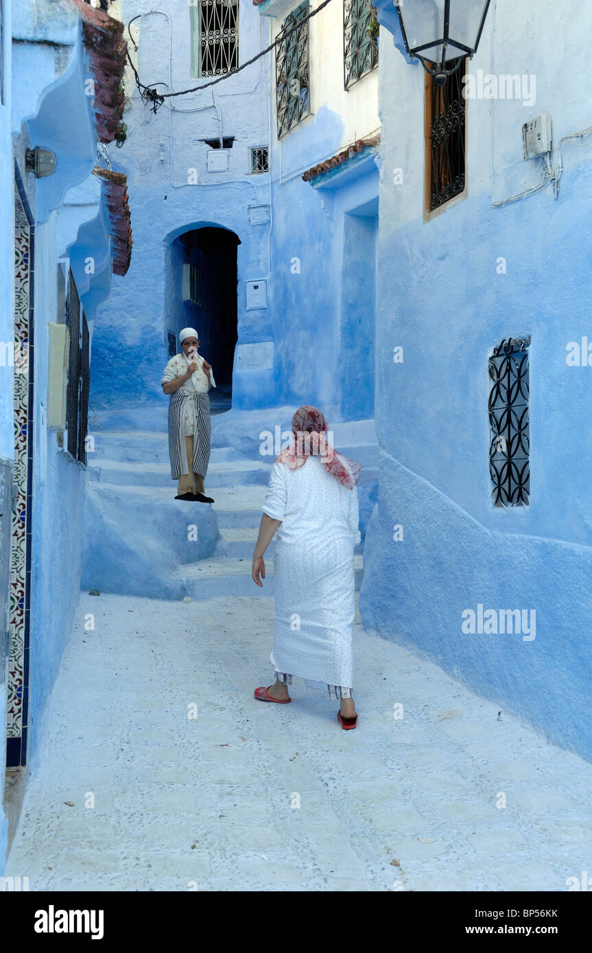 Couple of Moroccan Women or Neighbours Meet & Chat in the Narrow Blue Streets of Chefchaouen, Morocco - Stock Image