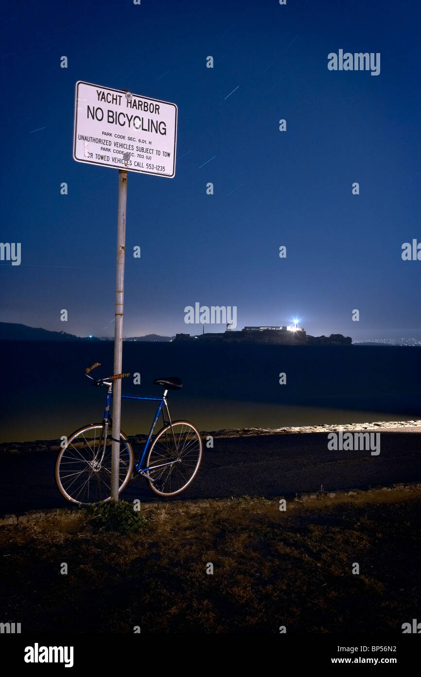 A push bike locked up to a no cycling sign at night with Alcatraz in the background. - Stock Image