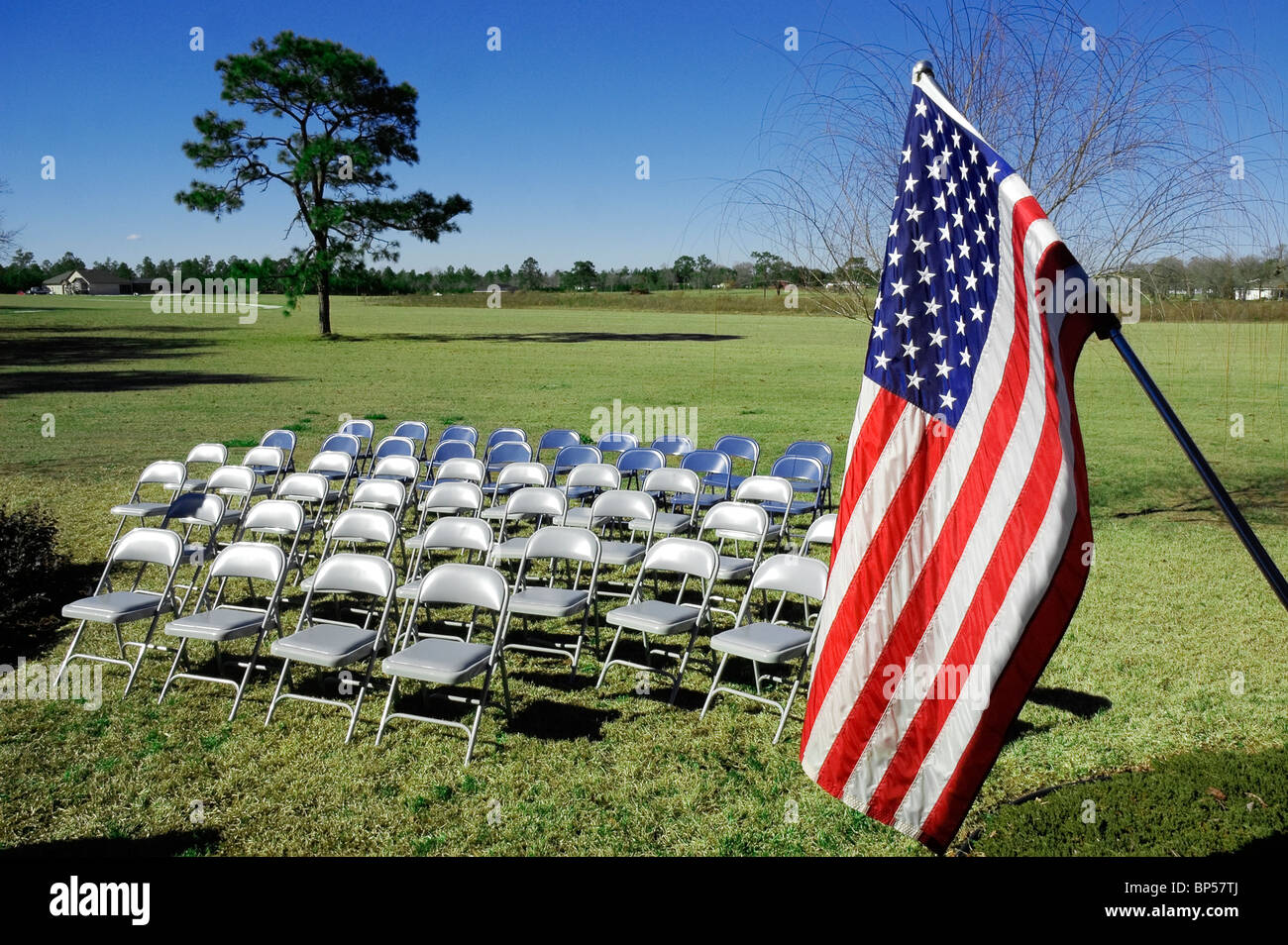 e77c17587e52 chairs and American flag set up outdoors - Stock Image