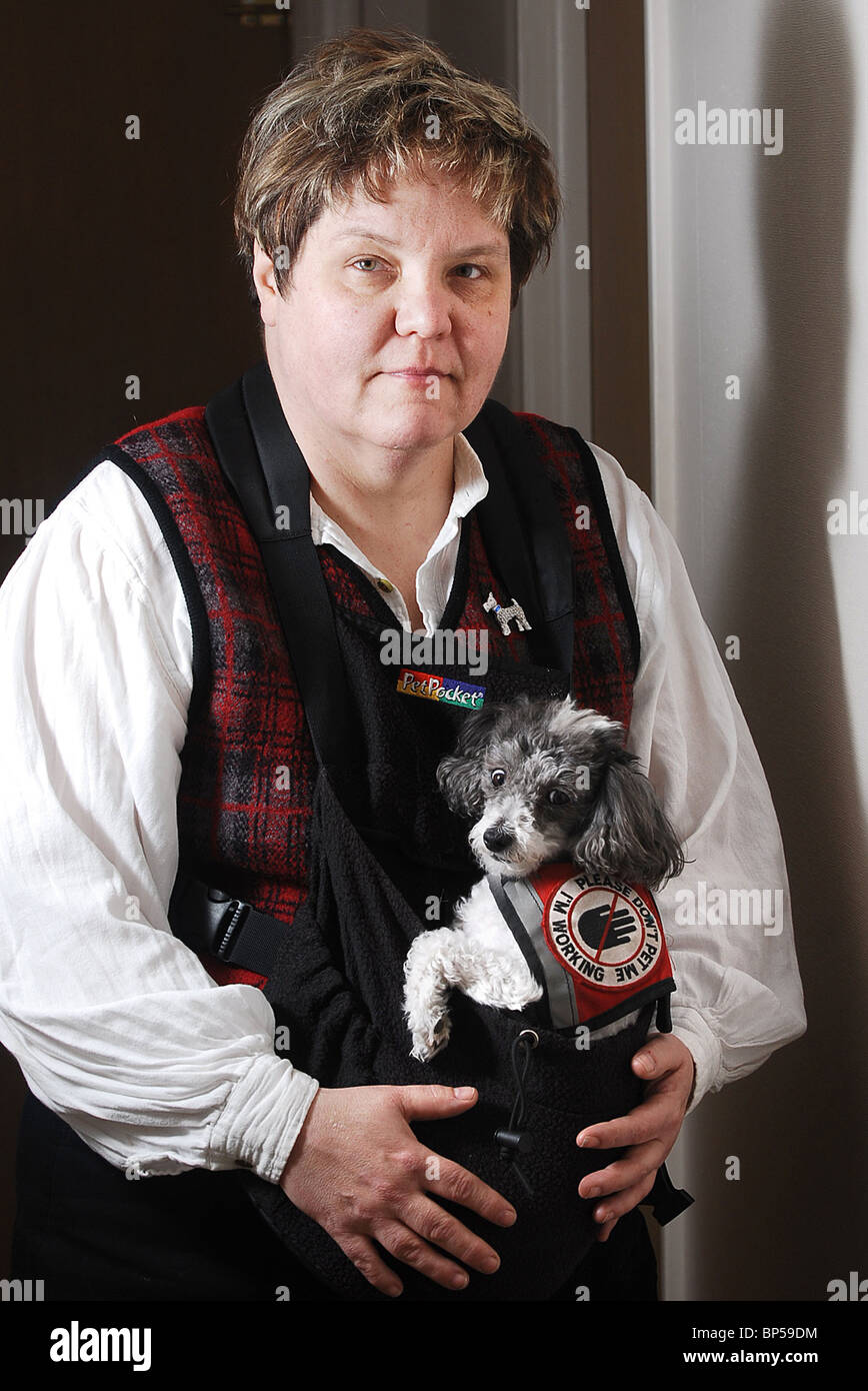 Woman with her service dog that she wears in a harness to help her with Post Traumatic Stress Disorder - Stock Image