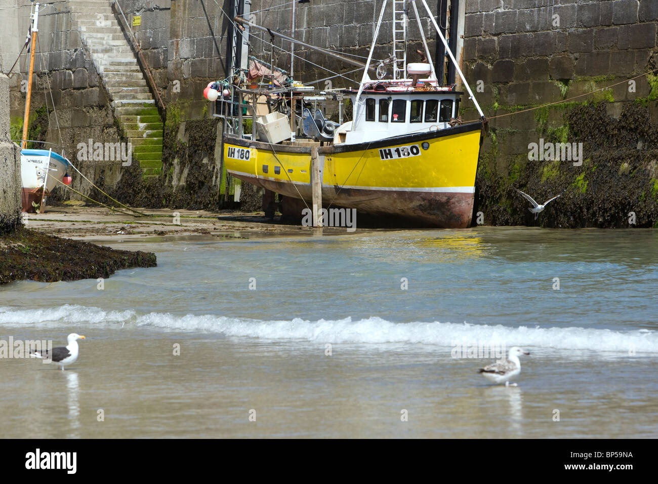 A yellow fishing boat in Newquay harbour at low tide. - Stock Image