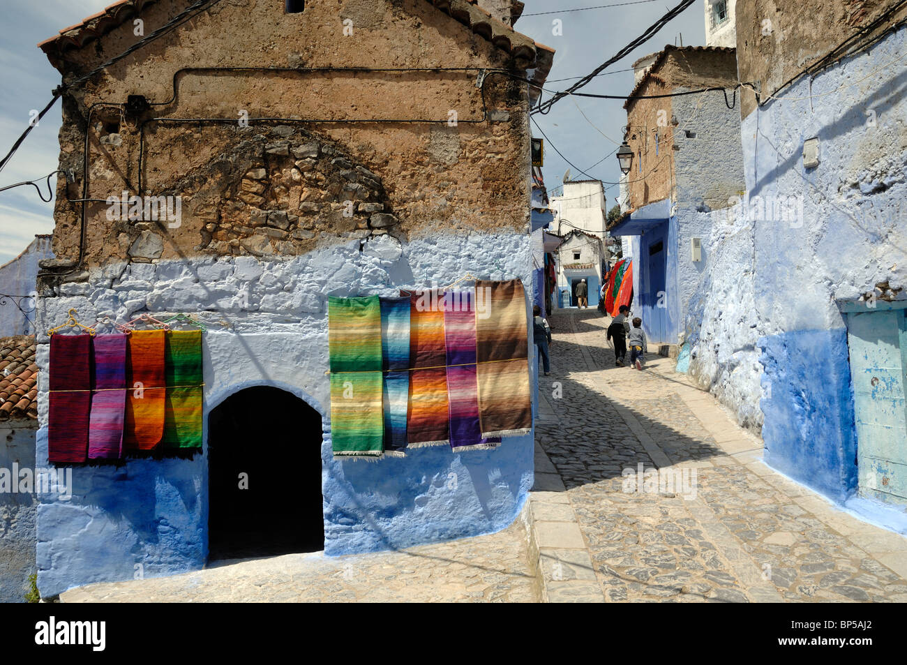 Street Scene in Chefchaouen with Display of Moroccan Carpets for Sale Hanging on Walls, & Blue Houses, Morocco - Stock Image