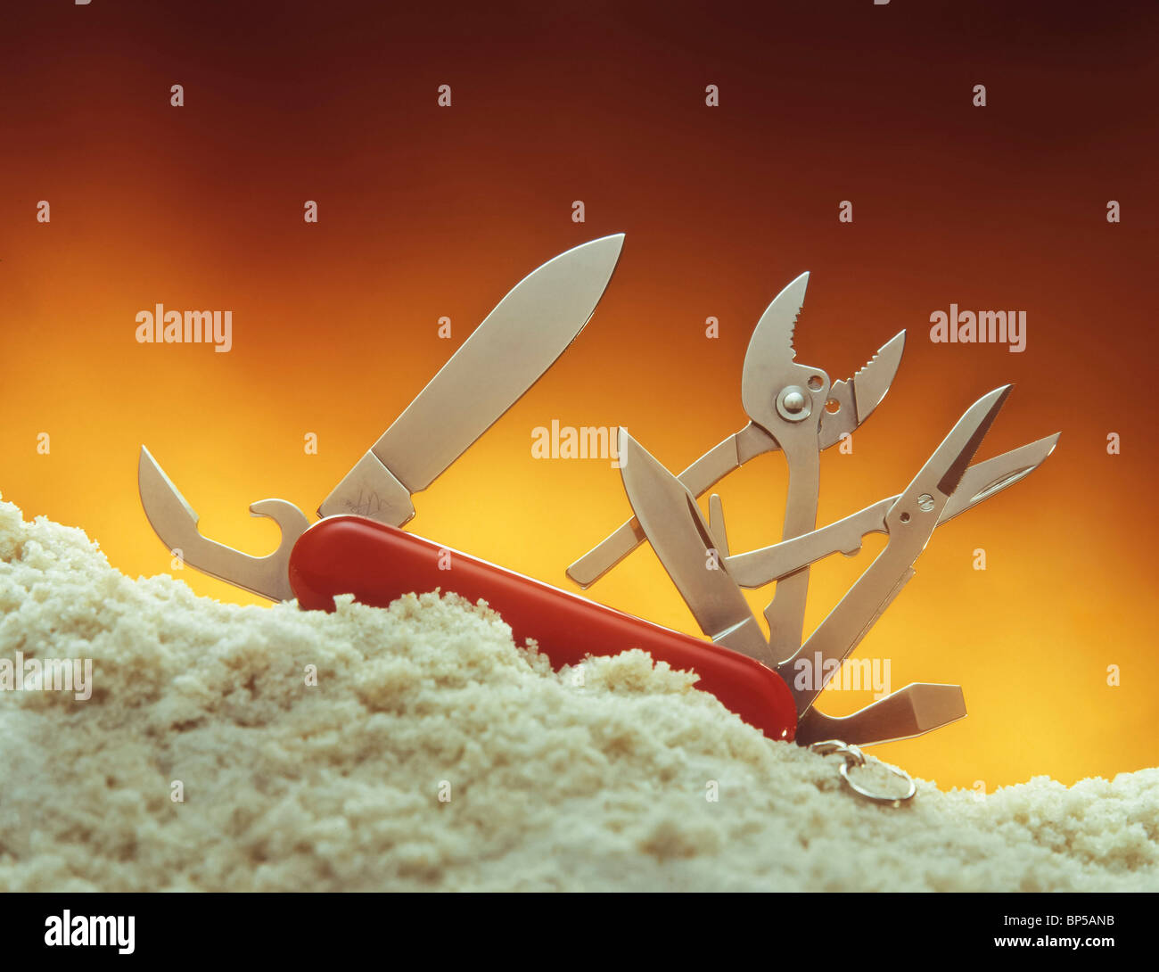 Swiss Army knife in white sand - Stock Image