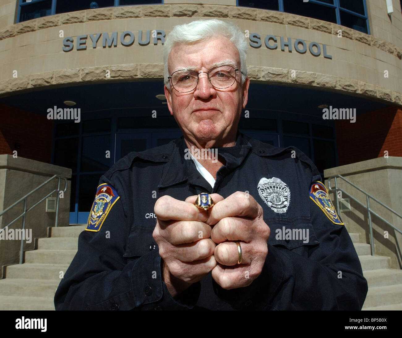 A Police officer shows off a class ring he found and returned it to it's owner some 30 years after High School - Stock Image