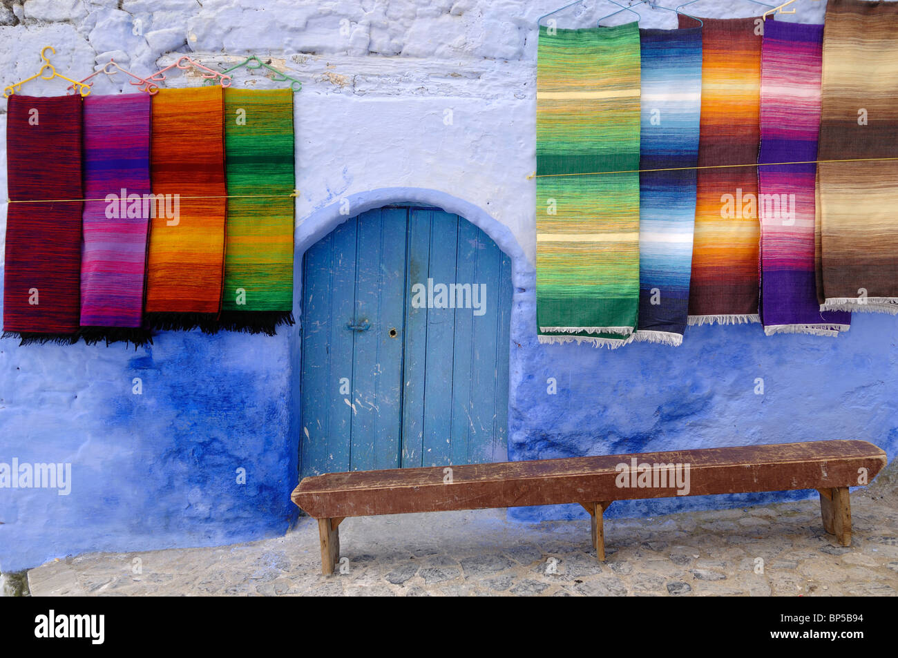 Display of Colourful Woven Carpets, Hanging Carpets or Rugs for Sale, Blue Door and Wooden Bench, Chefchaouen, Morocco - Stock Image
