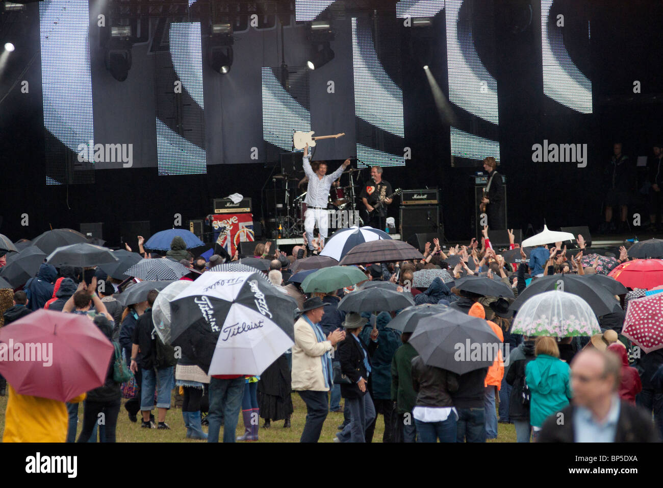 The Buzzcocks performing in front of an array of umbrellas at Vintage at Goodwood festival 2010 - Stock Image