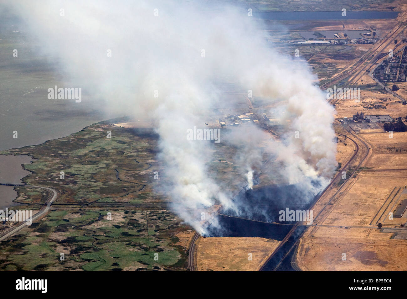 aerial view above controlled burn smoke fire rail road lines northern California - Stock Image