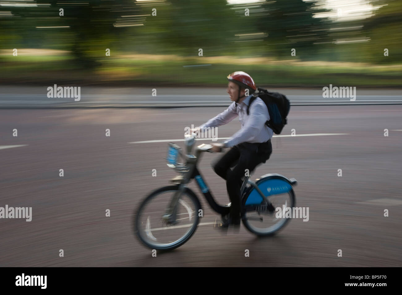 Commuter in London travels through Hyde Park using one of the Cycle Hire Scheme bicycles introduced to London in Stock Photo