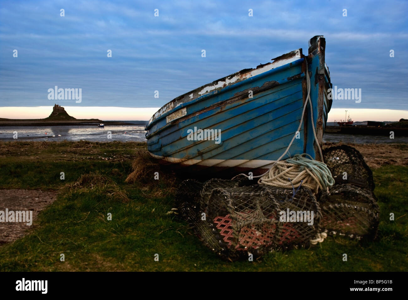 Northumberland, England; An Abandoned Boat And Traps On Shore With A View Of Lindisfarne (Holy Island) - Stock Image