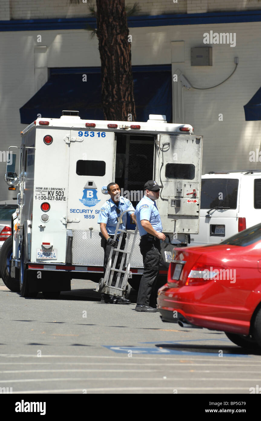 Armored car and currency delivery personnel enjoy their work while maintaining vigilance to maintain safety and - Stock Image
