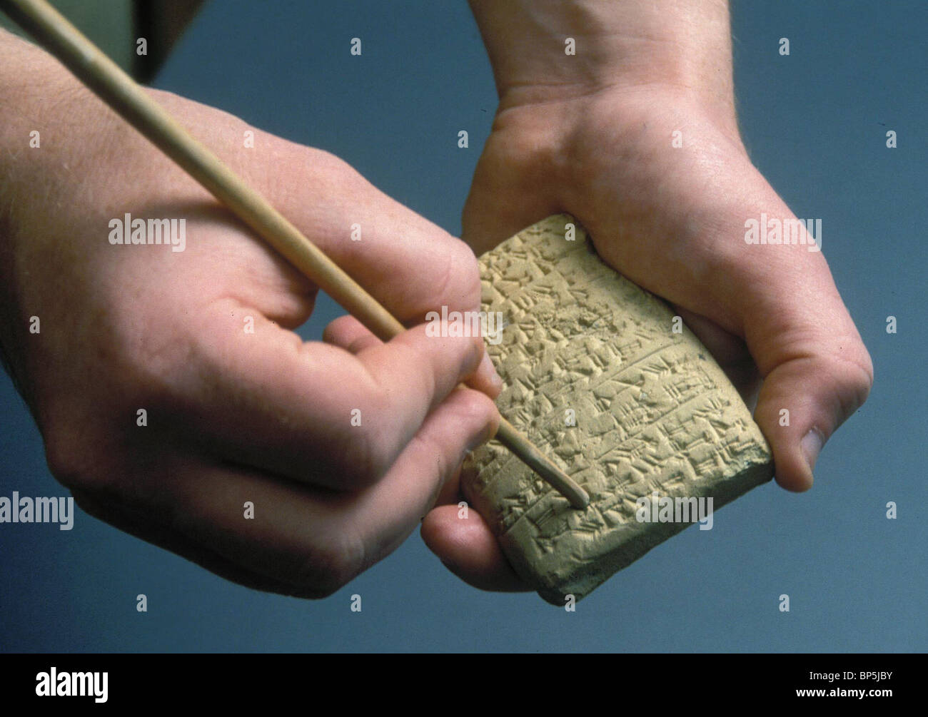 3739. WRITING A CUNIFORM TABLET BY PRESSING A WOODEN POINTER INTO WET CLAY - Stock Image